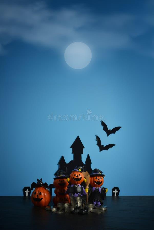 Cric-o-lanterne de potirons de Halloween avec des affaires croissantes de pile de pièce de monnaie d'argent sur le fond bleu-fonc photos libres de droits