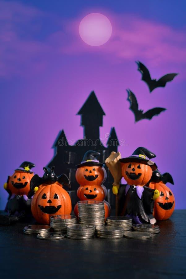 Cric-o-lanterne de potirons de Halloween avec des affaires croissantes de pile de pièce de monnaie d'argent sur le fond bleu-fonc photographie stock libre de droits