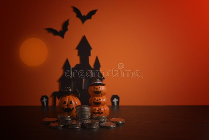 Cric-o-lanterne de potirons de Halloween avec des affaires croissantes de pile de pièce de monnaie d'argent sur le fond orange photographie stock libre de droits