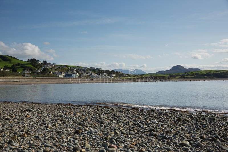 Criccieth beach and bay Wales UK coast town in summer with blue sky on a beautiful day. Criccieth North Wales UK historic coastal town in summer with blue sky on royalty free stock photography