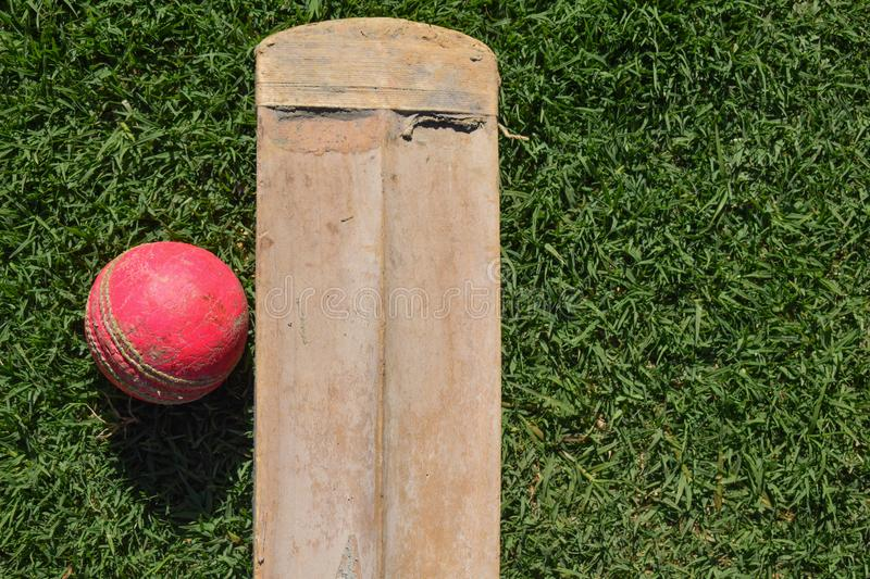 Cricket bat and ball on a green grass. Cricket equipments isolated on a green background. stock photos