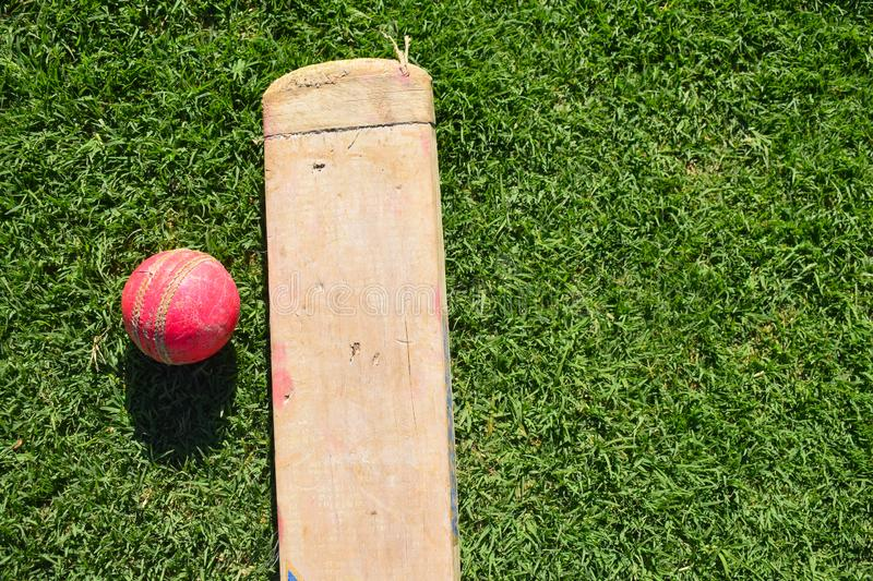 Cricket bat and ball on a green grass. Cricket equipments isolated on a green background. stock image