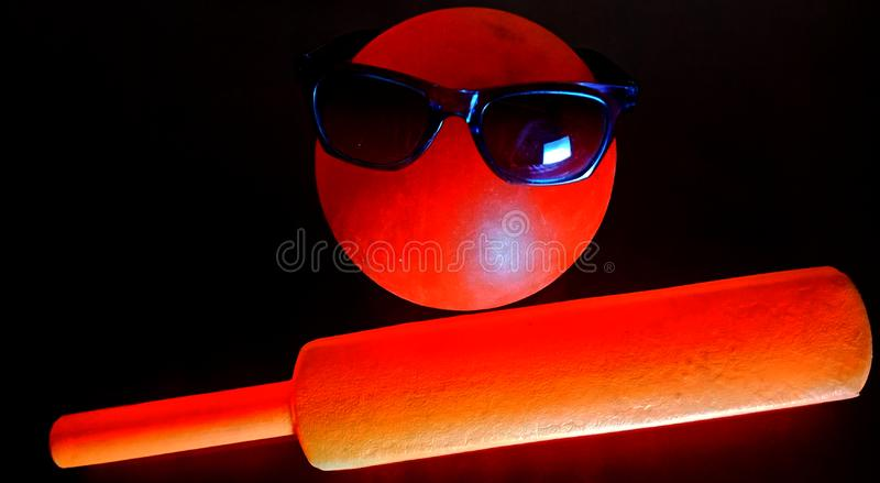 Cricket bat with football in red colour stock image. Smily, attractive, amazing royalty free stock photo