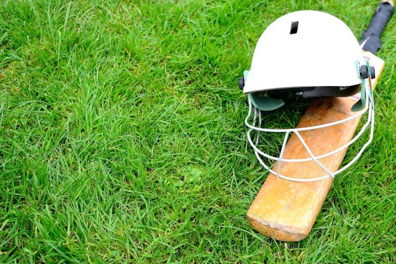 Cricket bat and helmet. On grass royalty free stock photo