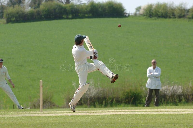A Cricket batsman hitting the ball stock images