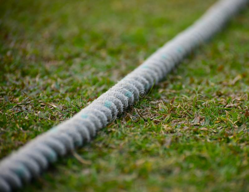 Cricket boundary rope isolated object stock photograph. The beautiful white cricket boundary rope isolated object with grass background stock photograph stock images
