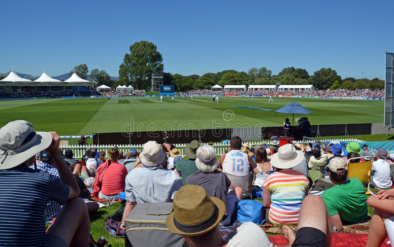 Cricket - Boxing Day Test Match Crowd at Hagley Oval Christchurch. Christchurch, New Zealand - December 26, 2014: Spectators sitting on the bank watching the stock image