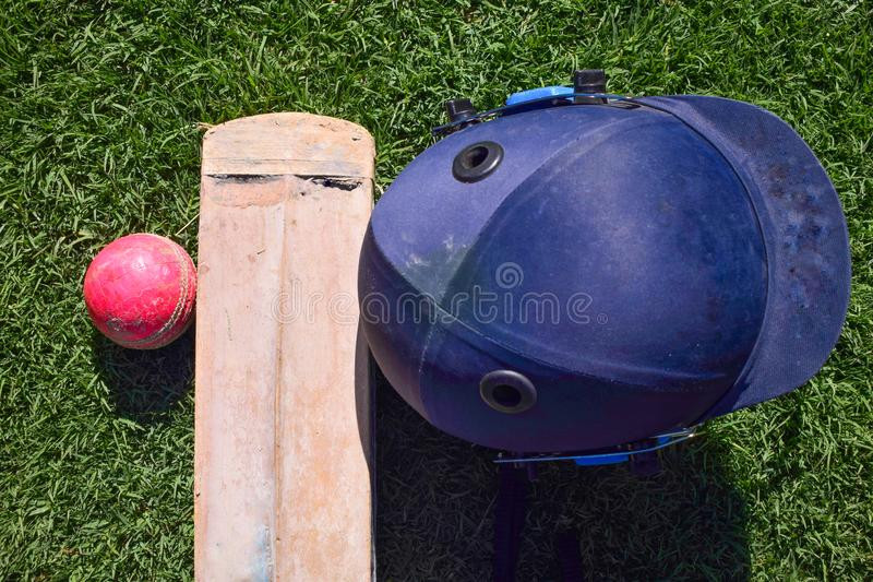 Cricket halmet ,bat, ball isolated on a green grass. royalty free stock images