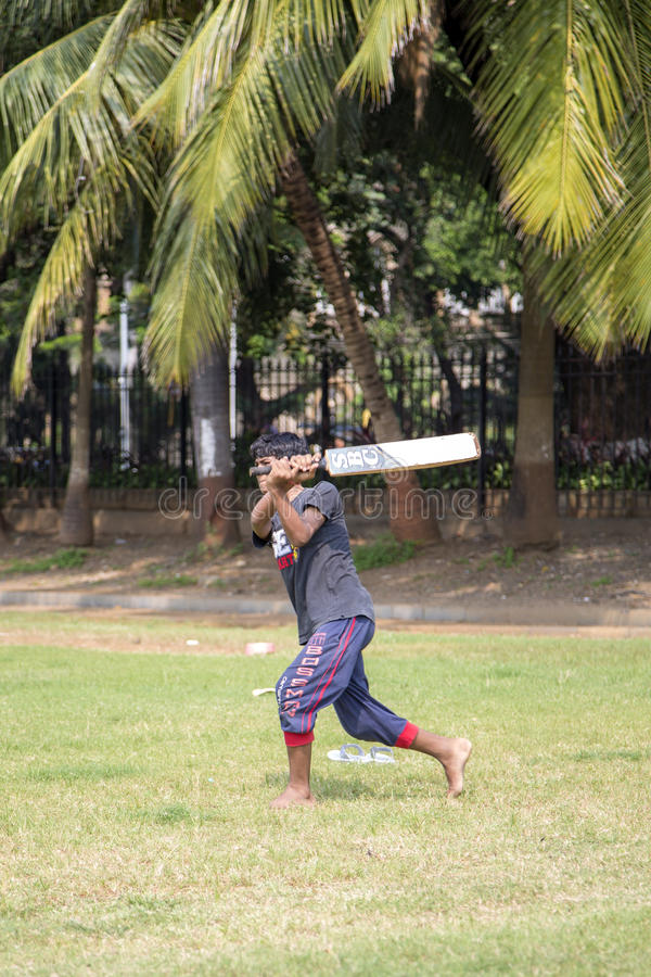Cricket in Mumbai, India. Man playing cricket in the central park at Mumbai. Cricket is the most popular sport in India. History of cricket in India is based on stock photo