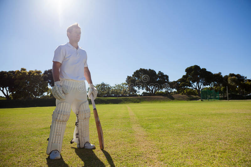 Cricket player with bat standing on grassy field. Full length of cricket player with bat standing on grassy field on sunny day stock images