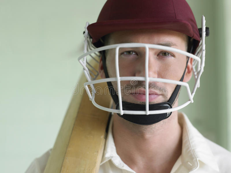 Cricket player In Helmet And With Bat. Closeup portrait of a cricket player wearing helmet and holding bat stock photo