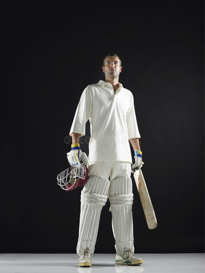 Cricket Player Holding Bat And Helmet. Full length of a cricket player holding bat and helmet against black background royalty free stock photo