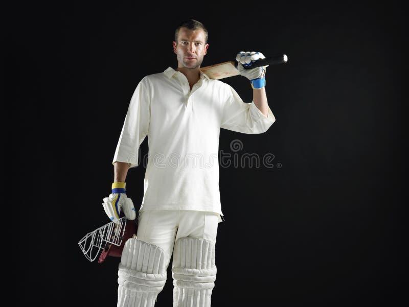 Cricket Player Holding Bat And Helmet. Portrait of a cricket player holding bat and helmet against black background stock photos