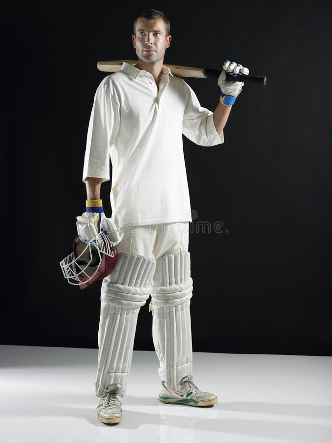 Cricket Player Holding Bat On Shoulder. Full length of a cricket player holding bat on shoulder against black background royalty free stock photography