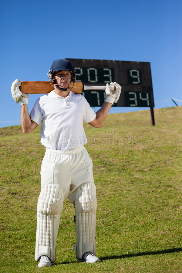 Cricket player holding bat while standing on field. Full length of cricket player holding bat while standing on field royalty free stock photos