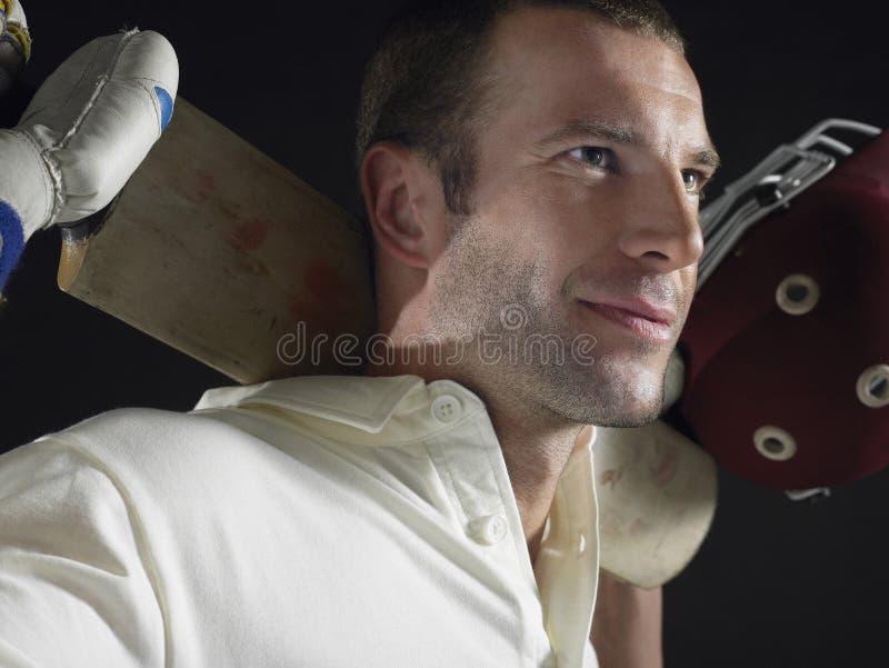 Cricket Player Holding Cricket Bat Behind Shoulders. Closeup of a cricket player holding cricket bat behind shoulders against black background stock image