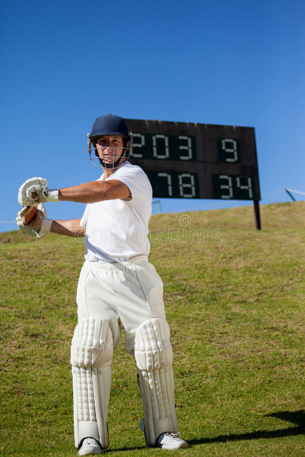 Cricket player swinging bat while standing at field. Confident cricket player swinging bat while standing against scoreboard at field royalty free stock photography
