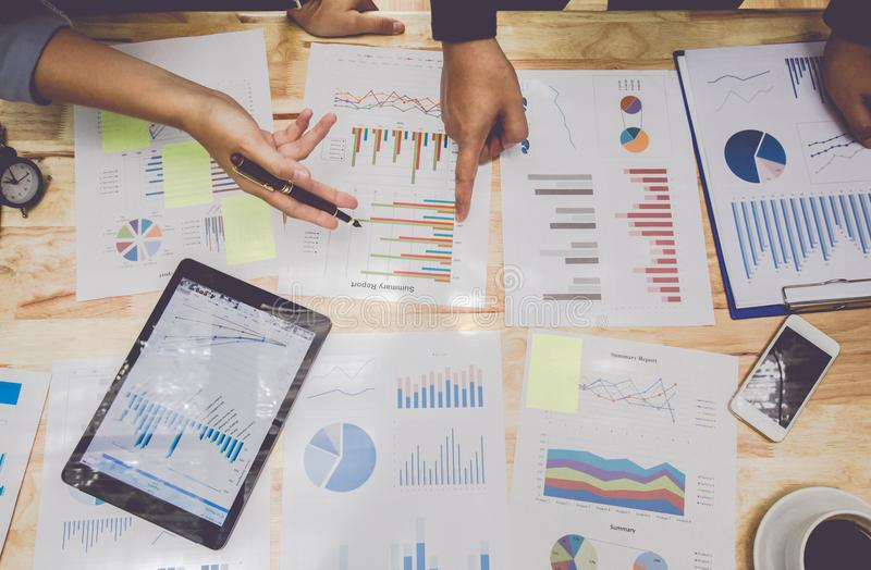 Crie o negócio ponto de reunião dos povos para discutir o gráfico para cima e para baixo da economia e o trabalho na tabela Vista foto de stock royalty free