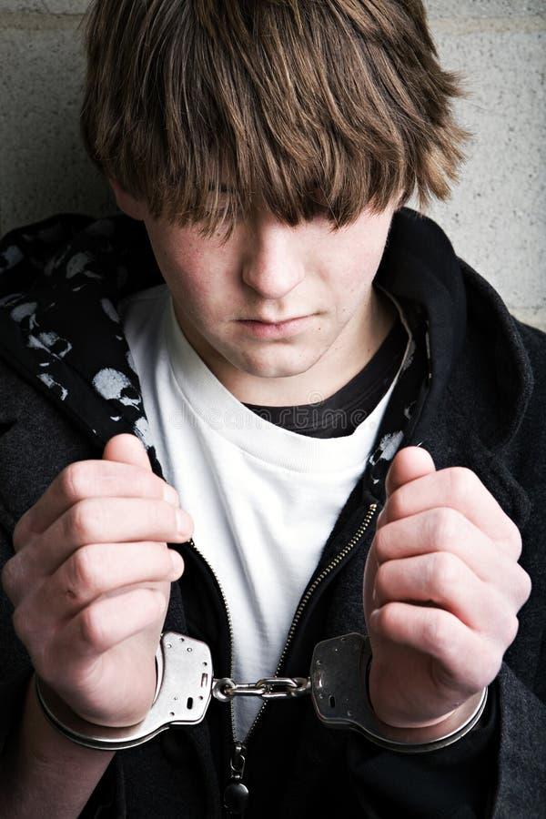 Crime de l'adolescence - gosse dans des menottes image stock