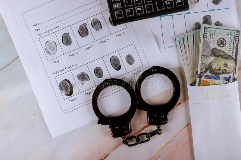 Crime financial tax police handcuffs on fingerprints crime page file calculator on US dollar banknotes. Pay tax, criminology, dollars, identification stock photo