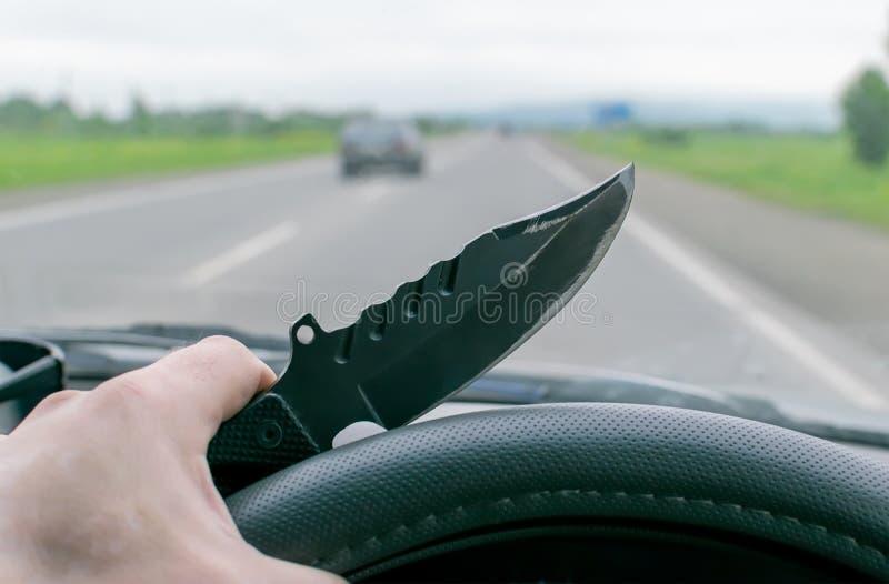 Crime, homme, conduisant une voiture tenant un couteau image libre de droits