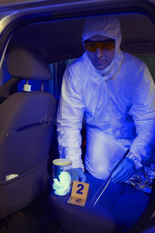 Police team working in ultraviolet light on collecting of traces and evidences stock image
