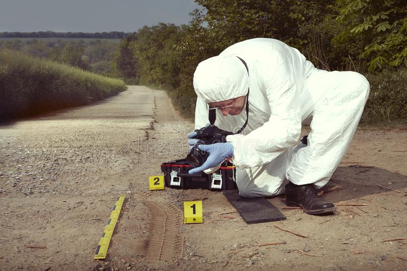Technician Criminologist photographing tire print left in dust of field way. Crime scene investigation - photographing of car tire print left on crime scene stock photography