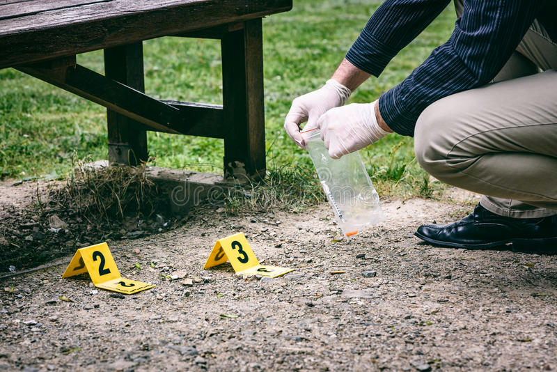 Crime scene investigation. Picking up the tossed syringe and putting it to the plastic bag stock image