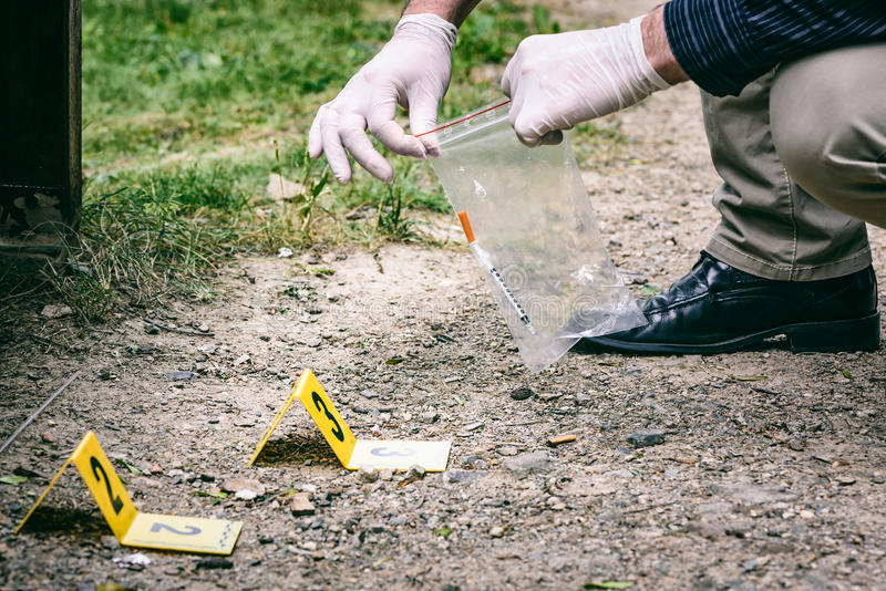 Crime scene investigation. Picking up the tossed syringe and putting it to the plastic bag royalty free stock images