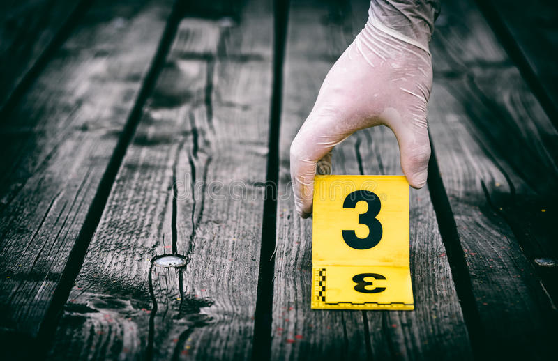 Crime scene investigation. Putting the crime scene marker on wood ground royalty free stock photography