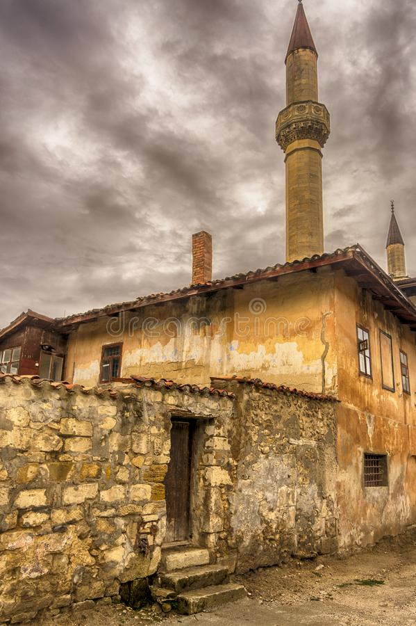 Crimea, Bakhchisarai. View of the Khan`s Palace from the old street in cloudy weather. Stone fence and gate to the yard. Crimea, Bakhchisarai. View of the Khan` royalty free stock image
