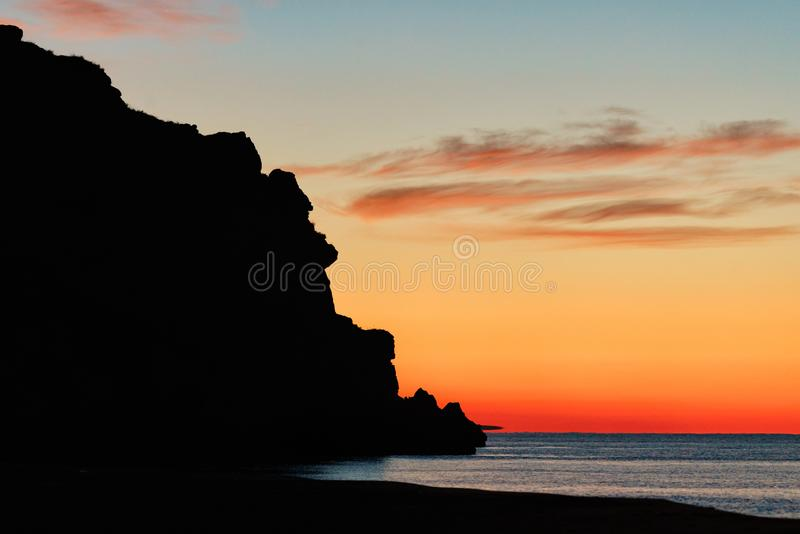 Crimea, Russia: Scenic sunset at Azov Sea coast known as Generals` Beaches. Rocky cliff silhouette at dusk. royalty free stock photos