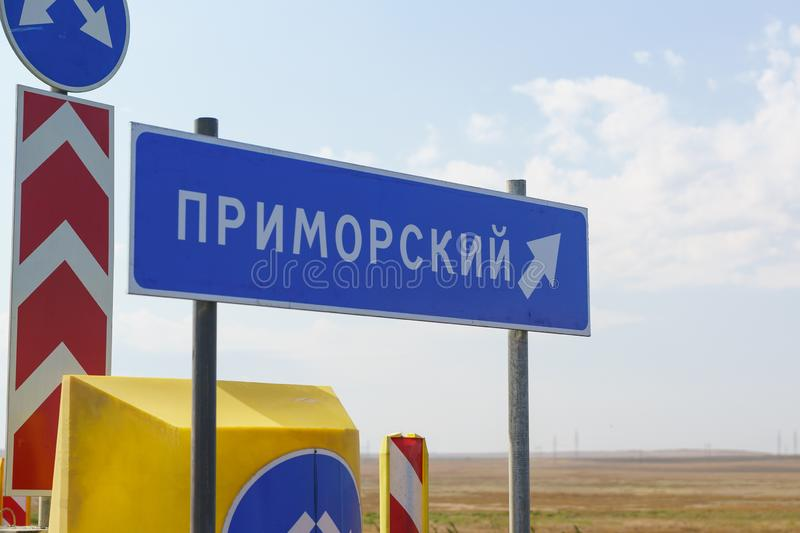 Blue sign with the name of the village on the road. The inscription in Russian stock photography