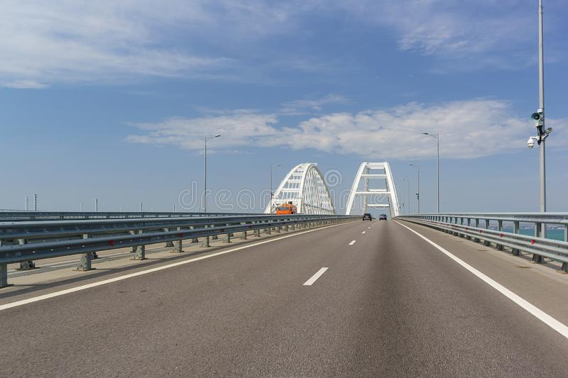 Crimean bridge across the Kerch Strait. Cars enter the arched span. Sunny day royalty free stock image