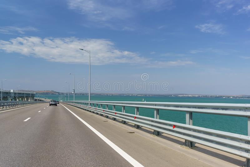 Crimean bridge across the Kerch Strait. Descent from the height of the navigable arch span. Ahead of Kerch and the sea is calm. royalty free stock photography
