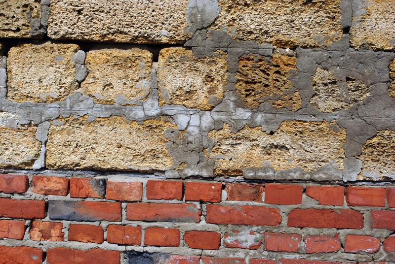 Crimean coquina rock blocks with cement lines on red bricks, wall of two different materials, close up texture stock images