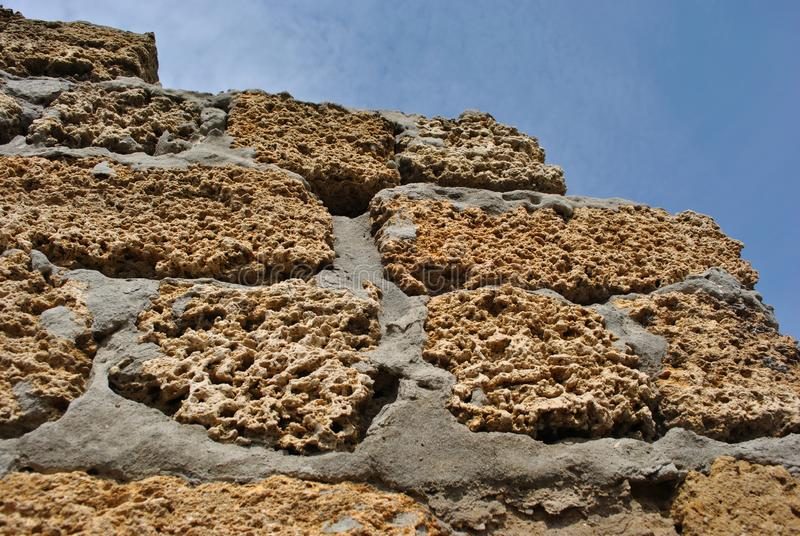 Crimean coquina rock blocks with cement ruined farm wall close up texture, blue sky stock photos