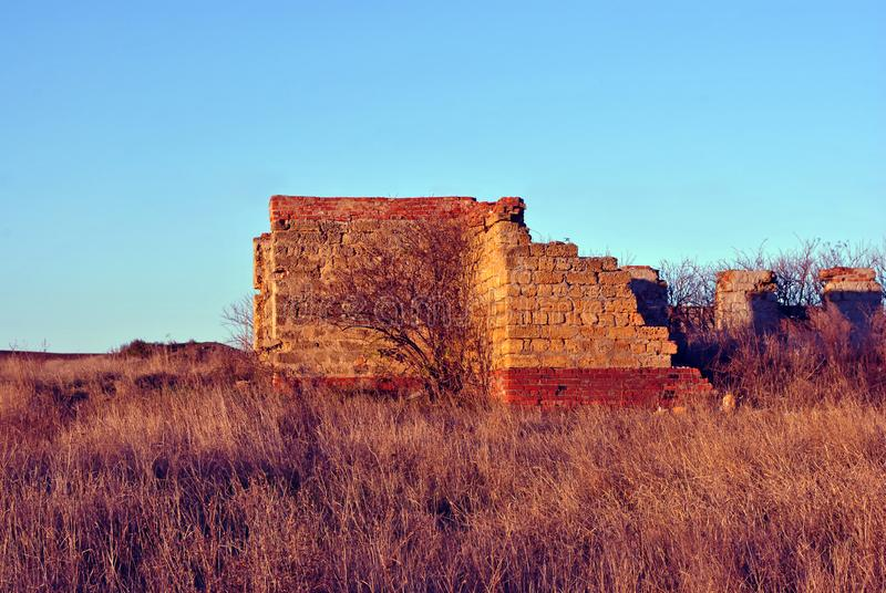 Crimean coquina rock blocks ruined farm wall, dry weathered grass field with elderberry bushes without leaves behind, blue sky stock photo