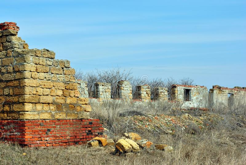 Crimean coquina rock blocks ruined farm walls, dry weathered grass field with elderberry bushes without leaves stock photos
