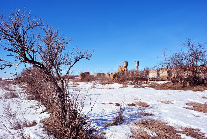 Crimean coquina rock blocks ruined farm walls, two water towers, dry weathered grass field covered with snow, elderberry bushes stock photos