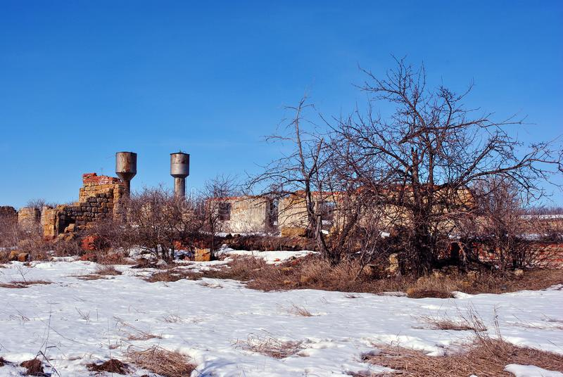 Crimean coquina rock blocks ruined farm walls, two water towers, dry weathered grass field covered with snow, elderberry bushes. Without leaves growing along royalty free stock images