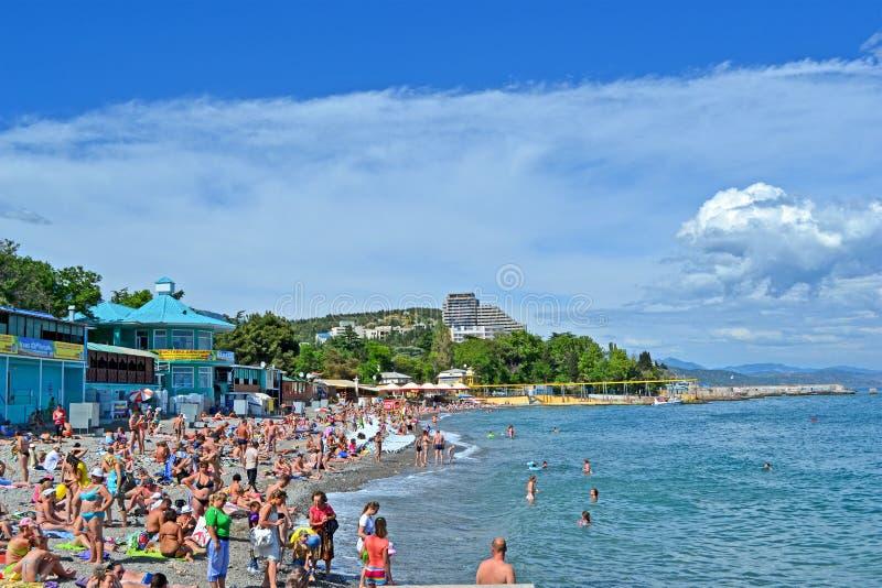 Crimean resort, public pebble beach, Alushta,. ALUSHTA, UKRAINE - JUN 01: People on the public pebble beach near Black Sea in Alushta, Ukraine on June 01, 2013 royalty free stock photography