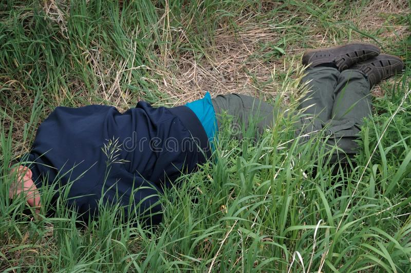 Criminal, accident or social problems. The corpse of a tramp in the grass or alcoholic intoxication. Killing a homeless man. Dead royalty free stock photo