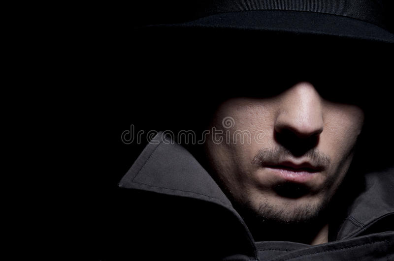 Criminal. Young criminal in shadow, isolated on a black background stock images
