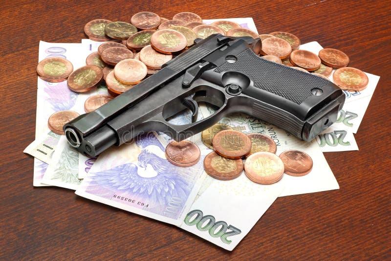 Criminal activity. Gun on money symbolising money-related criminality royalty free stock photos