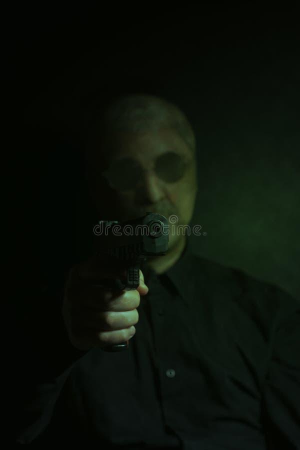 Criminal bandit man wearing a stocking mask holds a gun. On black background stock images