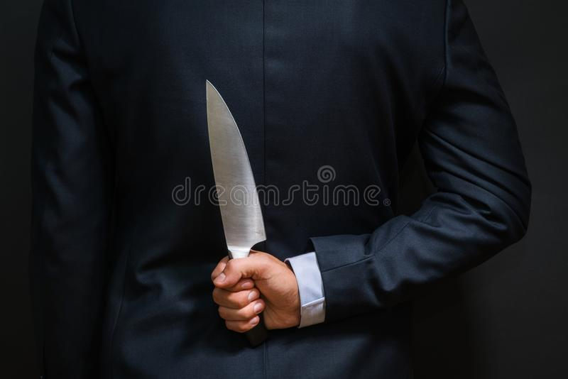 Criminal with big knife hidden behind his back. Cold weapon, bur royalty free stock image