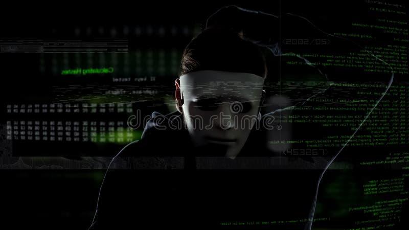 Criminal cibernético en la máscara blanca que corta el sistema de seguridad, actividades ilegales, ataque imagen de archivo