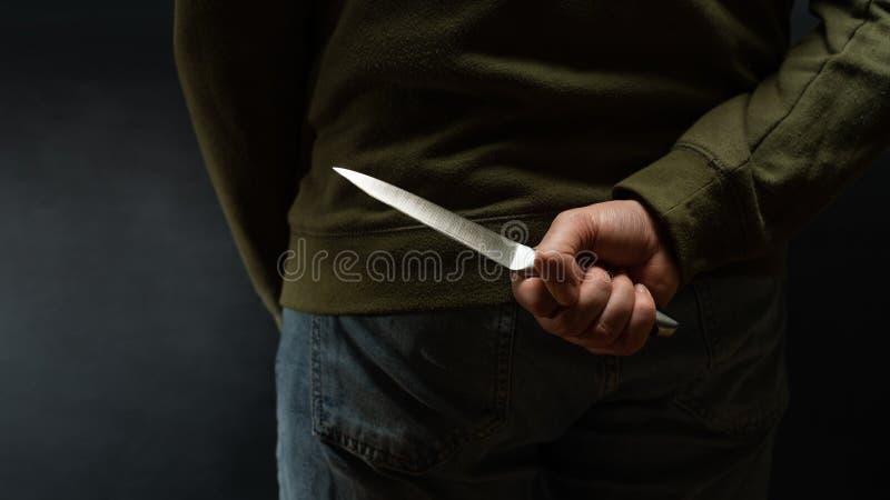 Criminal con el arma del cuchillo ocultada detrás la suya detrás imágenes de archivo libres de regalías