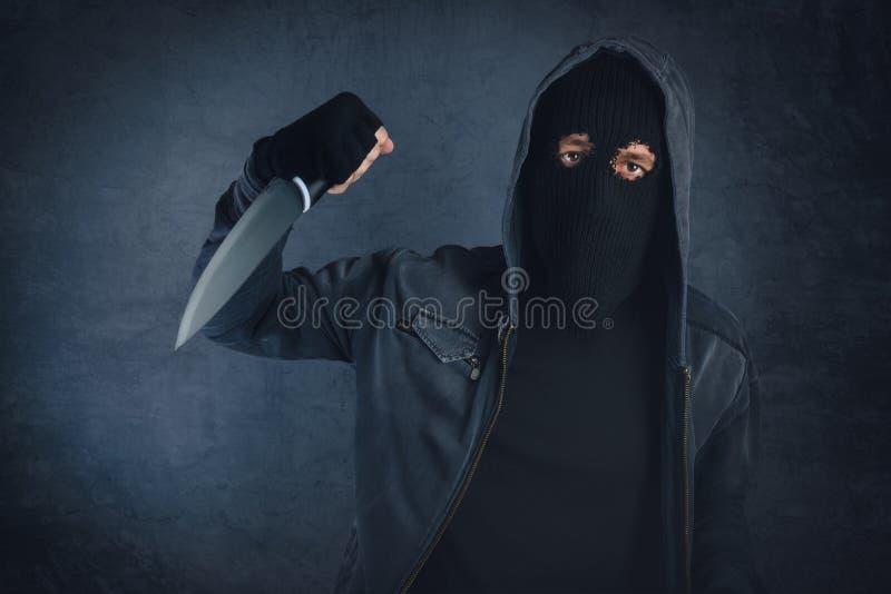 Criminal con el cuchillo afilado threating, el punto de vista de la víctima foto de archivo